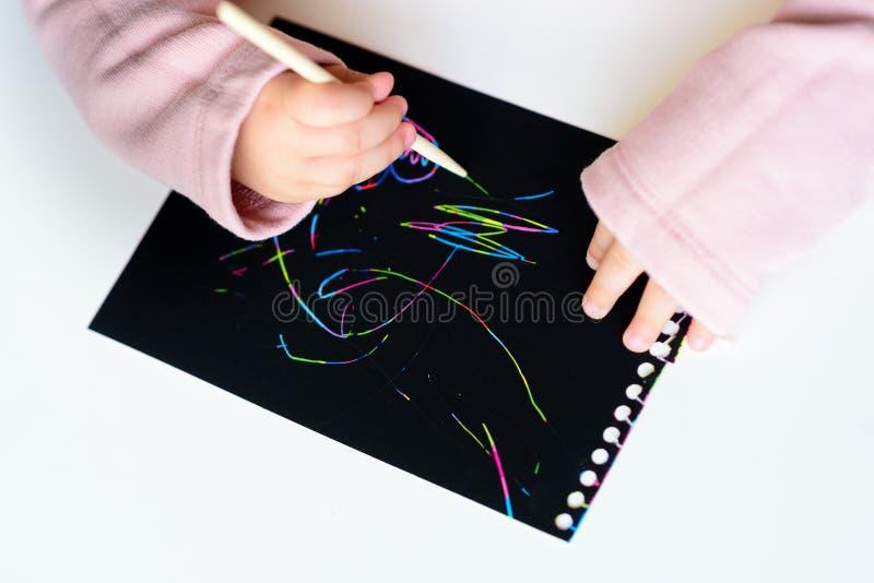 Fermez-vous des mains d'un dessin de petit enfant sur le papier de peinture d'éraflure magique avec le bâton de dessin photos stock