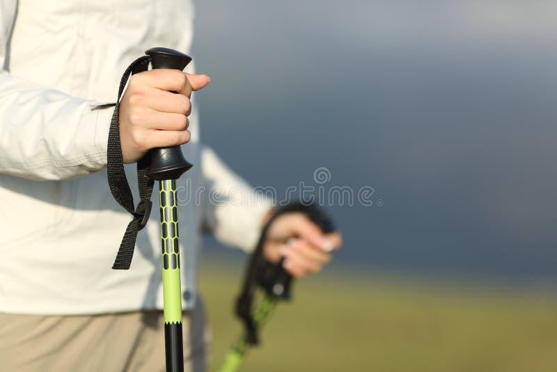 Fermez-vous des mains d'un randonneur marchant avec des poteaux photos libres de droits