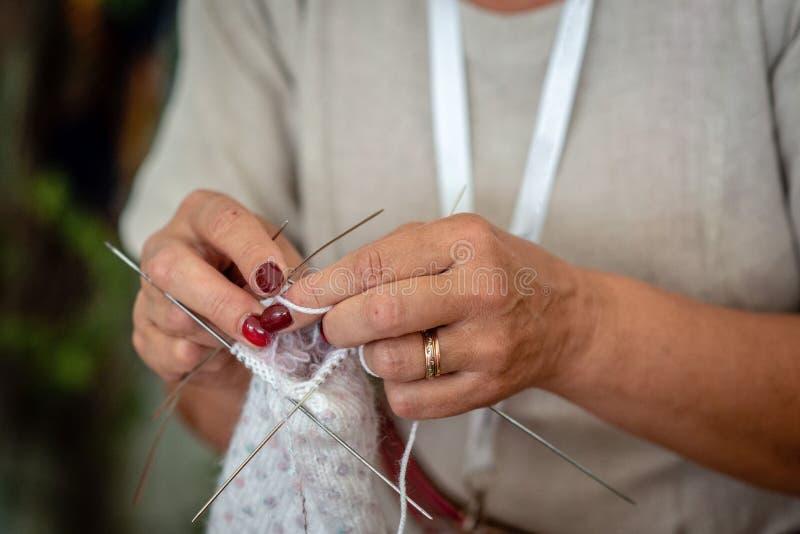 Fermez-vous des mains d'un tricotage de femme agée - Image photographie stock