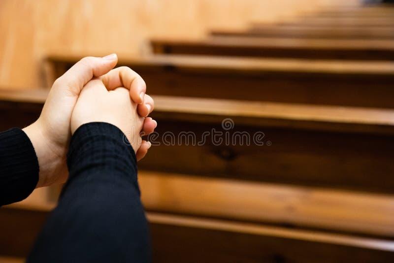 Fermez-vous des mains d'une femme priant à l'église photos libres de droits