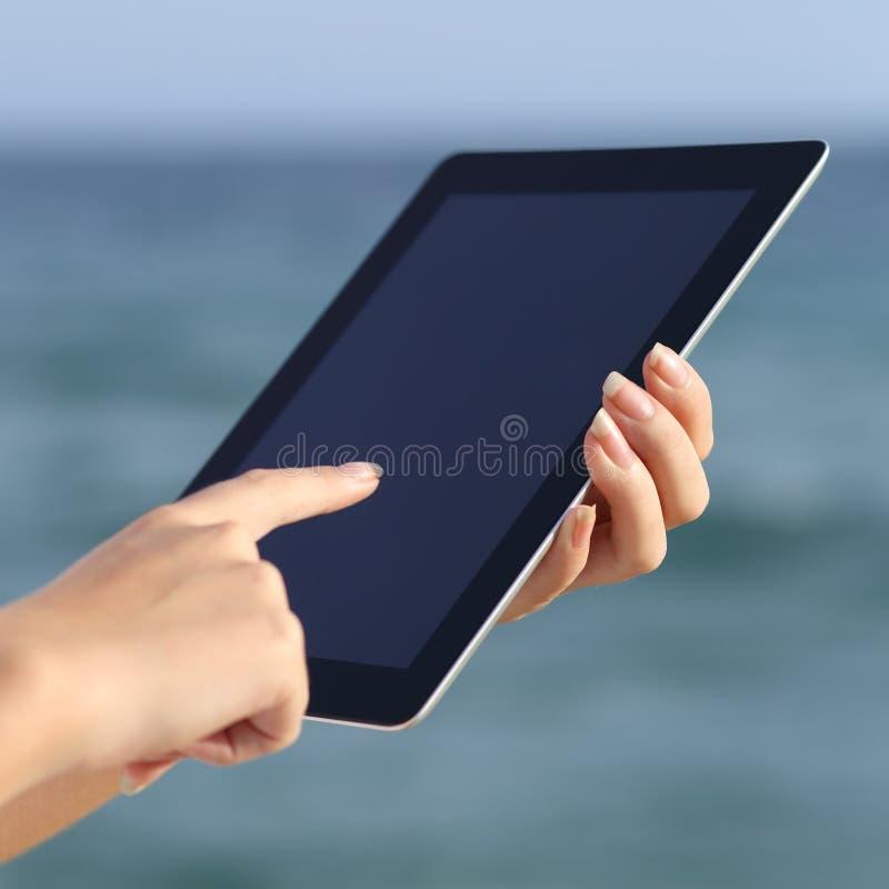 Fermez-vous des mains d'une femme tenant et passant en revue un comprimé numérique sur la plage photo libre de droits