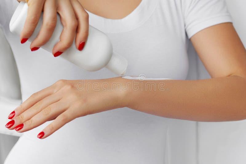 Fermez-vous des mains d'une fille tenant une bouteille de crème de main de lotion Main jugeant la bouteille en plastique cosmétiq photo libre de droits