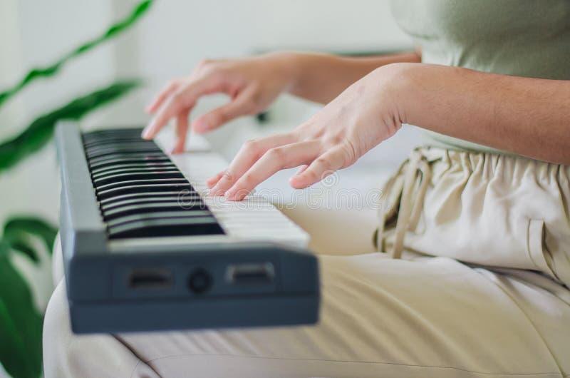 Fermez-vous des mains d'une jeune femme jouant l'instrument de musique de clavier de jeux à la maison photos libres de droits
