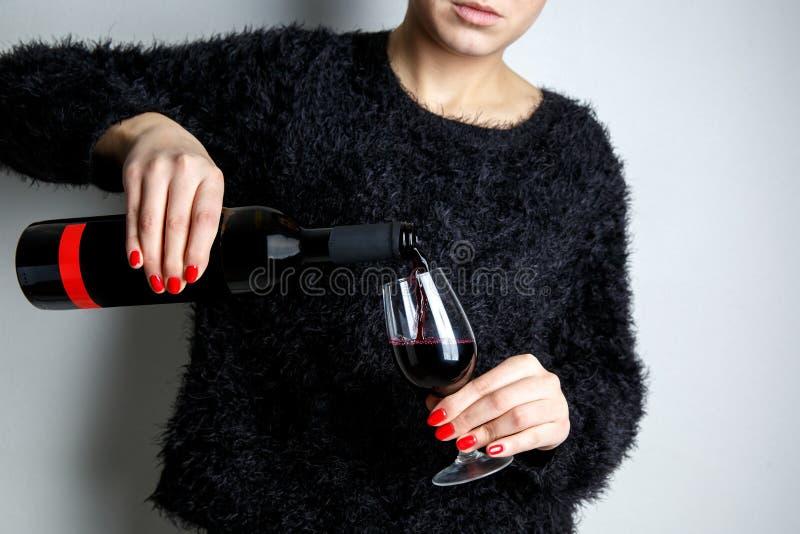 Fermez-vous des mains d'une jeune femme versant le vin rouge dans un verre d'une bouteille photo stock