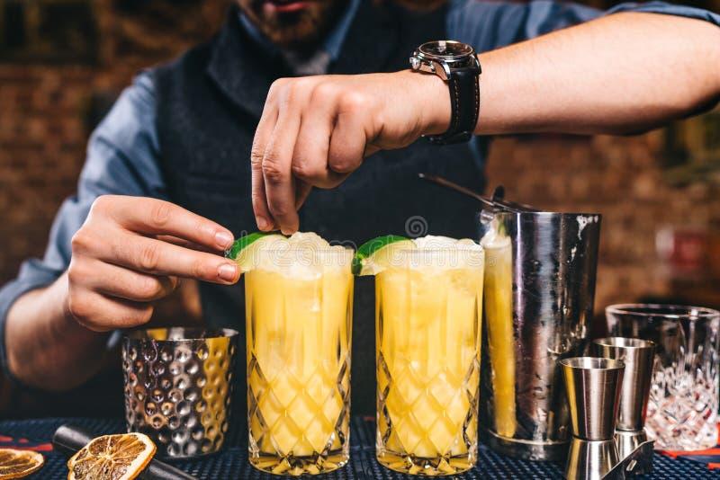 Fermez-vous des mains de barman garnissant et préparant les cocktails de fantaisie La vodka a basé les cocktails oranges à la bar photos stock