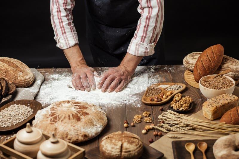 Fermez-vous des mains de boulanger malaxant la pâte et faisant le pain avec une goupille photographie stock libre de droits