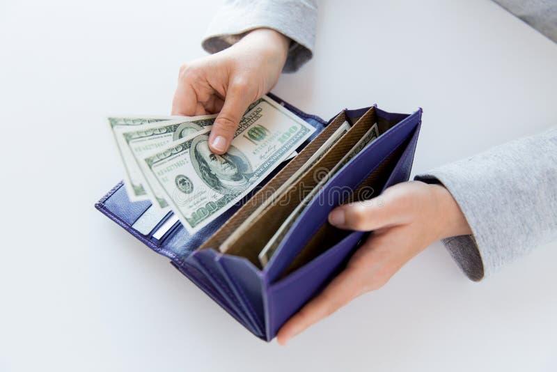 Fermez-vous des mains de femme avec le portefeuille et l'argent photos stock