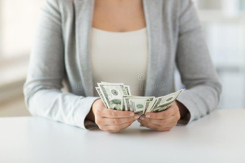 Fermez-vous des mains de femme comptant argent de dollar US image stock