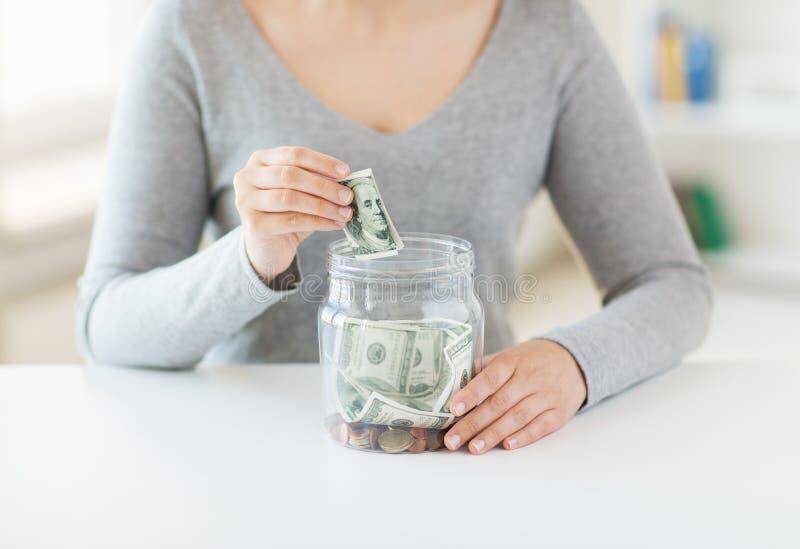 Fermez-vous des mains de femme et de l'argent du dollar dans le pot photographie stock