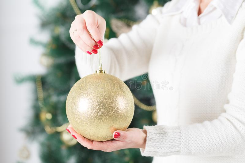 Fermez-vous des mains de femme tenant la boule de goold de Noël Décoration, vacances et concept de personnes photos stock