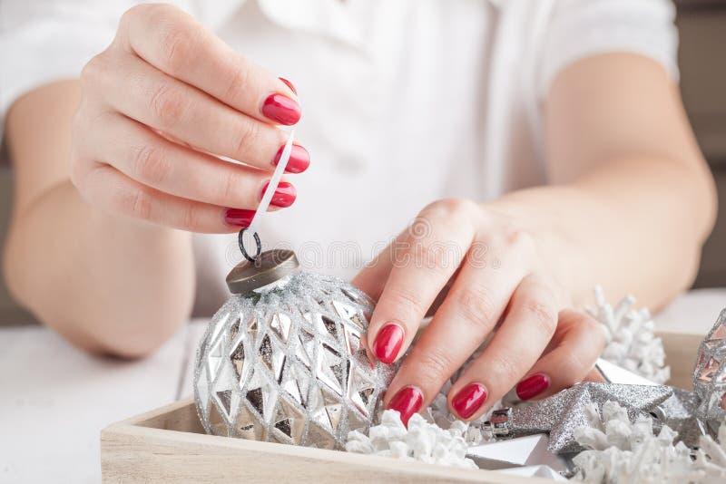 Fermez-vous des mains de femme tenant la boule de goold de Noël Décoration, vacances et concept de personnes photographie stock