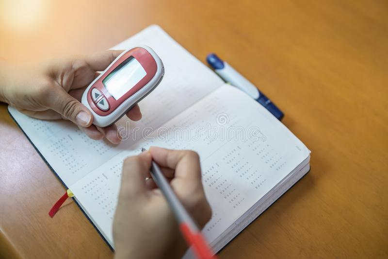 Fermez-vous des mains de femme tenant le mètre de glucose et le stylo d'utilisation pour écrire le taux du sucre dans le sang de  photos libres de droits