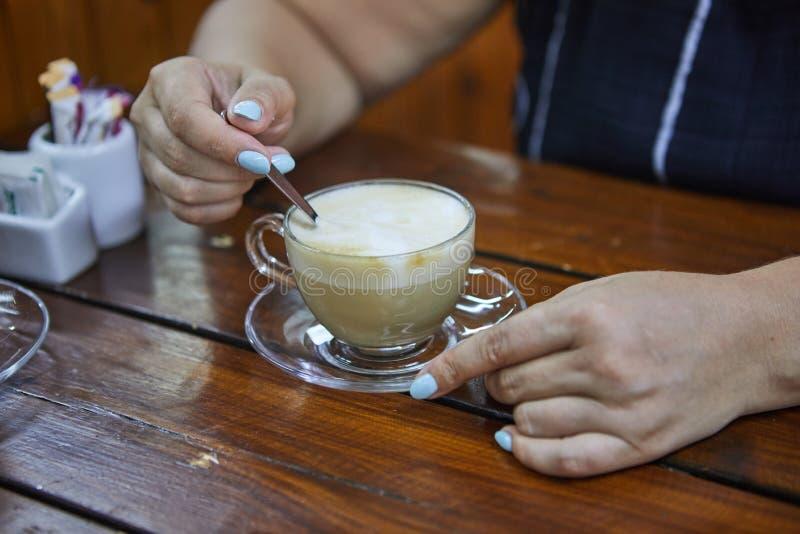 Fermez-vous des mains de femme tenant une tasse de café de cappuccino Femelle avec la cuvette de caf? image stock