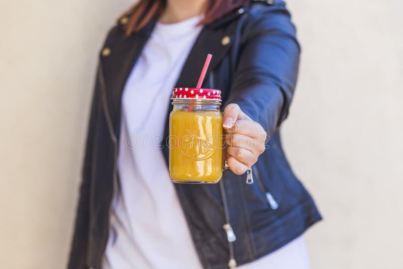 Fermez-vous des mains de femme tenant une tasse de jus d'orange lifestyle image libre de droits