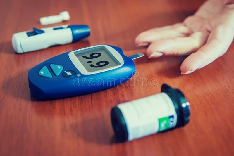 Fermez-vous des mains de femme utilisant le bistouri sur le doigt pour vérifier le taux du sucre dans le sang images stock