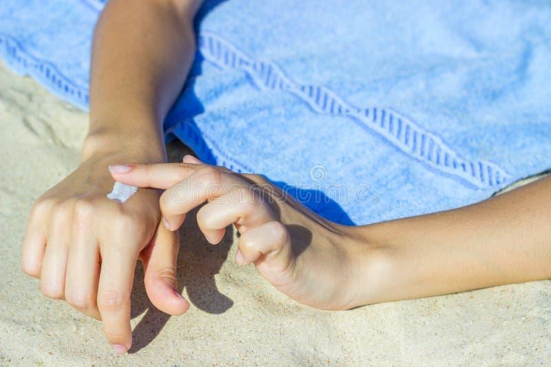 fermez-vous des mains de femmes recevant la crème de sunblock photo stock