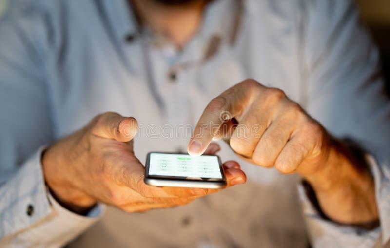 Fermez-vous des mains de jeune homme utilisant le smartphone dans la d?pendance de t?l?phone et le concept mobile de jeu photos stock