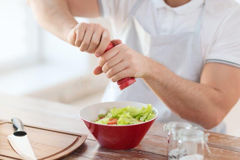 Fermez-vous des mains de mâle assaisonnant la salade dans une cuvette image stock