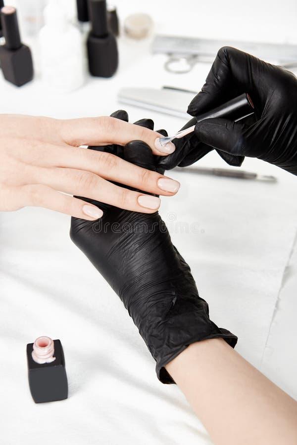 Fermez-vous des mains de manucure dans les gants appliquant le poli de gel images stock