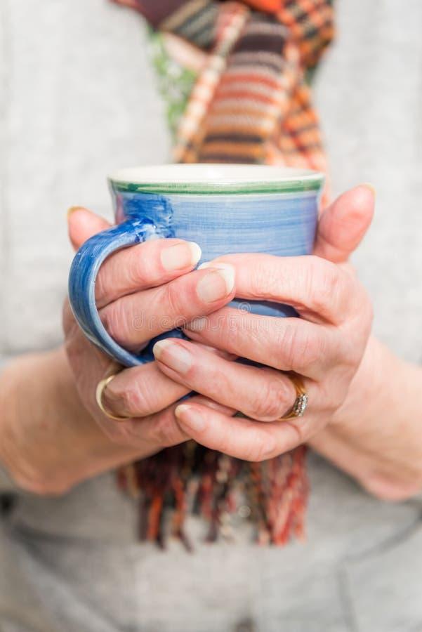 Fermez-vous des mains de retraités tenant une boisson chaude images libres de droits