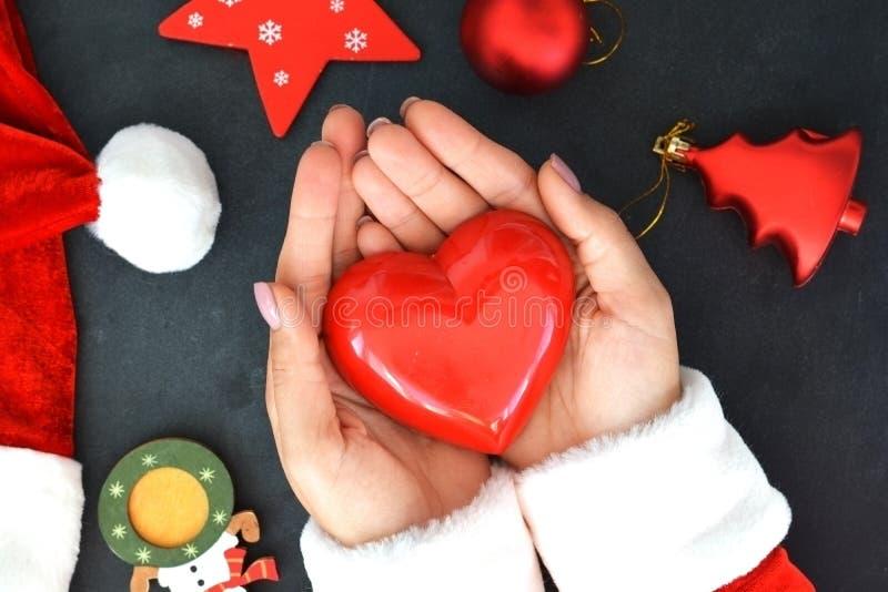 Fermez-vous des mains de Santa's tenant la forme rouge de coeur sur le fond de Noël images stock