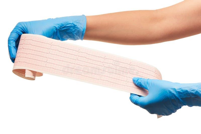 Fermez-vous des mains du docteur féminin dans les gants chirurgicaux stérilisés par bleu avec des résultats d'ECG sur le papier photographie stock libre de droits