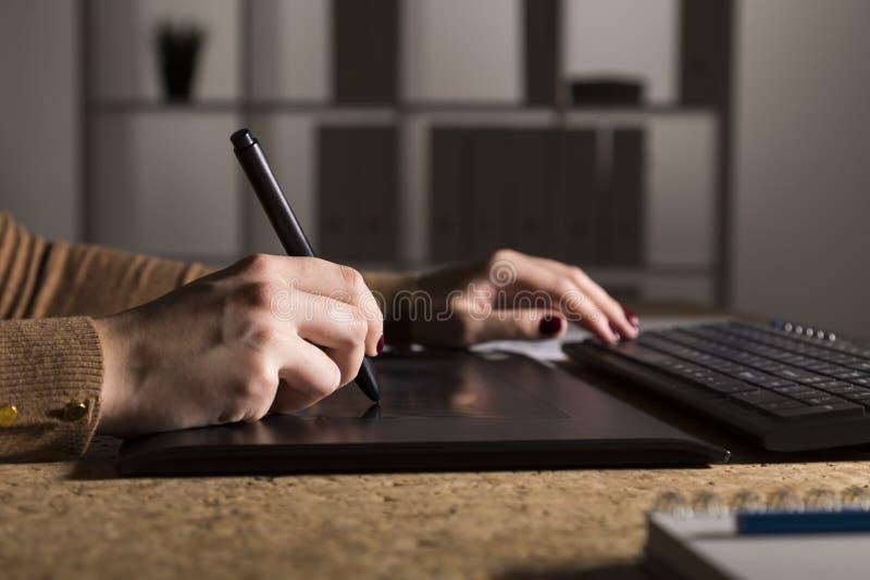 Fermez-vous des mains du ` s de femme dessinant sur sa protection et dactylographie photographie stock libre de droits