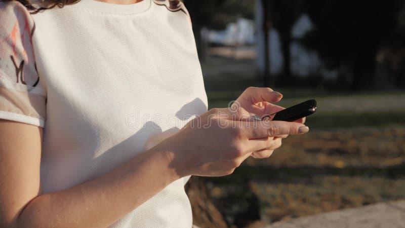 Fermez-vous des mains du ` s de femme utilisant le smartphone se reposant sur le banc en parc au coucher du soleil Beau service d image stock