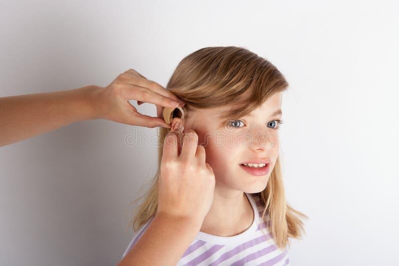 Fermez-vous des mains du ` un s de docteur adaptant une prothèse auditive pour une jeune fille photographie stock libre de droits