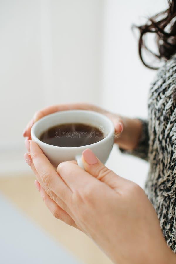 Fermez-vous des mains femelles avec une tasse de caf? image stock