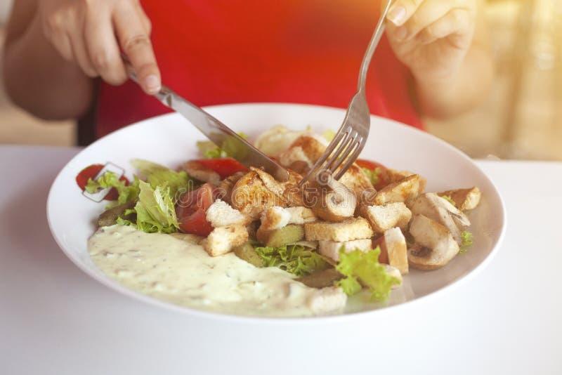 Fermez-vous des mains femelles coupant la salade délicieuse avec le couteau et la fourchette au restaurant image stock