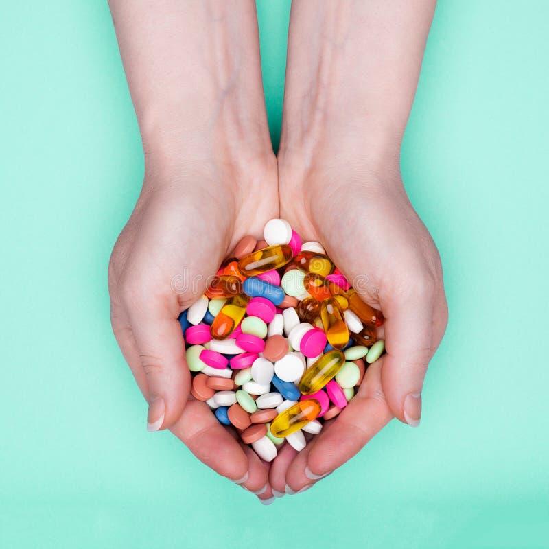 Fermez-vous des mains femelles tenant le tas des pilules colorées de médicament au-dessus du fond bleu en pastel images libres de droits