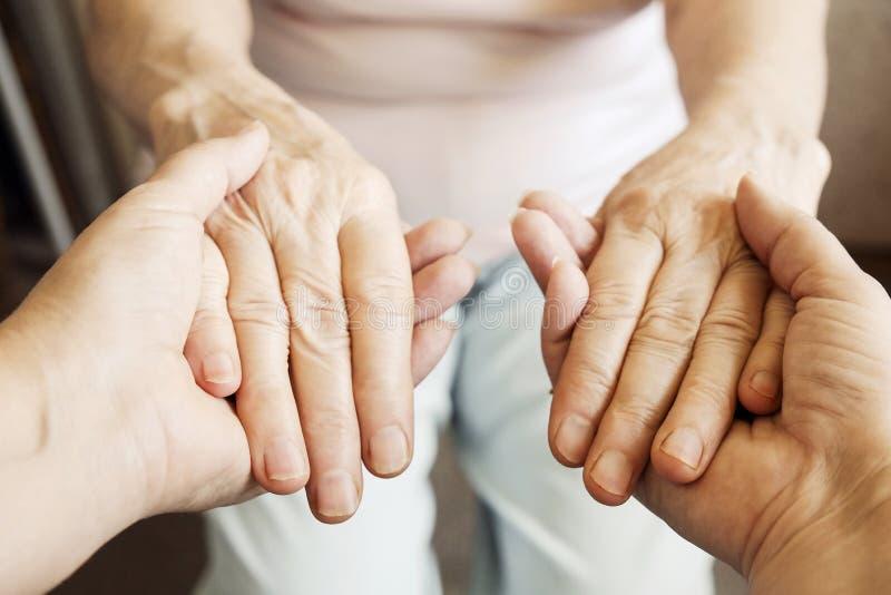 Fermez-vous des mains mûres de la femme et de l'infirmière Soins de santé donnant, maison de repos Amour parental de grand-mère L photos stock