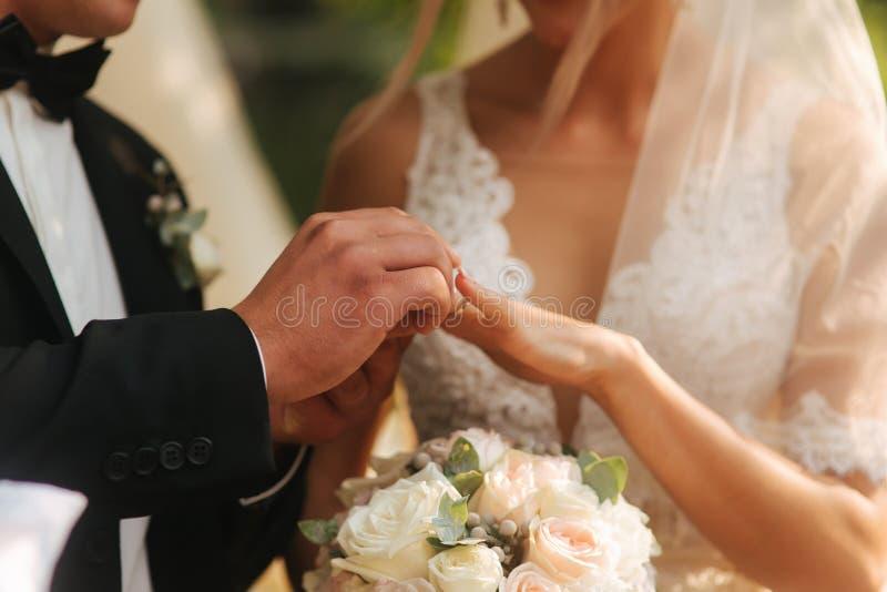 Fermez-vous des mains marié et jeune mariée portant un anneau photos libres de droits