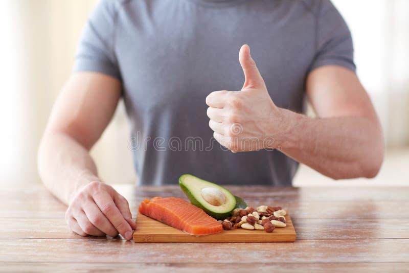 Fermez-vous des mains masculines avec des riches de nourriture en protéine image libre de droits