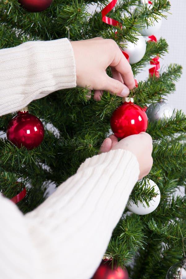 Fermez-vous des mains masculines décorant l'arbre de Noël image libre de droits