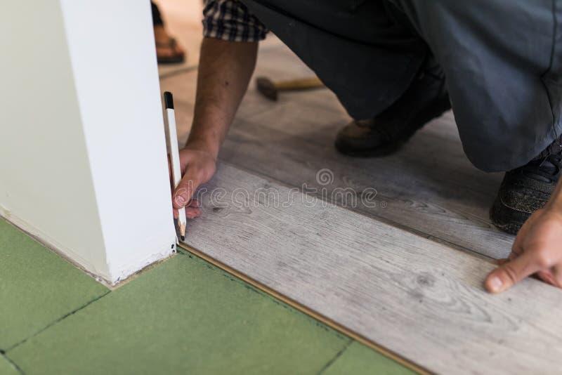 Fermez-vous des mains masculines intalling le plancher en bois photo stock