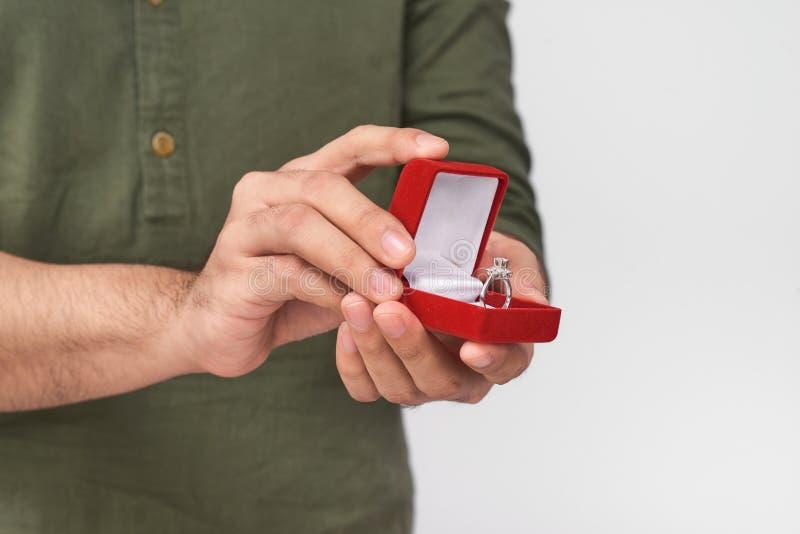 Fermez-vous des mains masculines tenant l'anneau et le boîte-cadeau de mariage images libres de droits