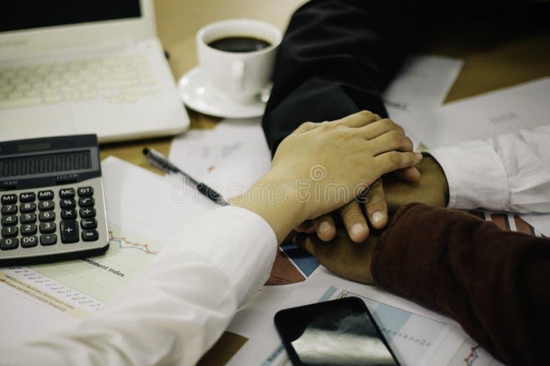 Fermez-vous des mains sur les hommes d'affaires, endroit sur des documents de résultats de société sur la table en bois, avec des photos libres de droits