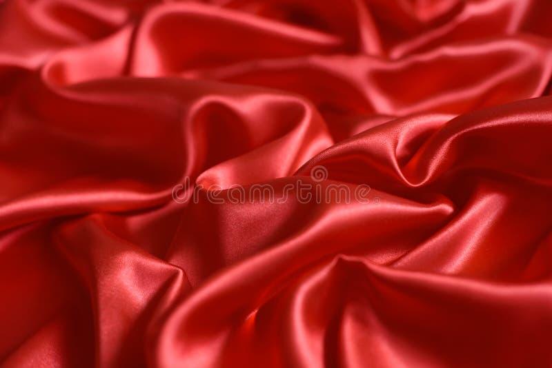 Fermez-vous des ondulations sur le tissu en soie rouge image libre de droits