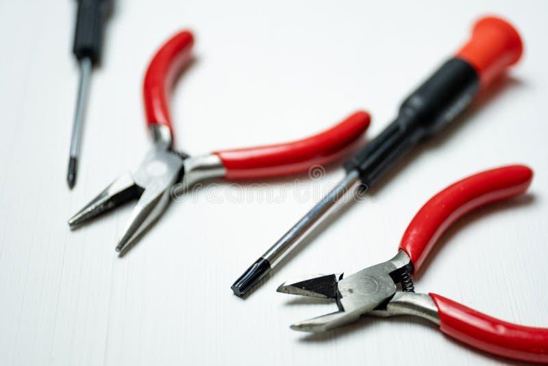 Fermez-vous des outils pour l'électronique de réparation et tout autre travail de précision sur le fond blanc image stock