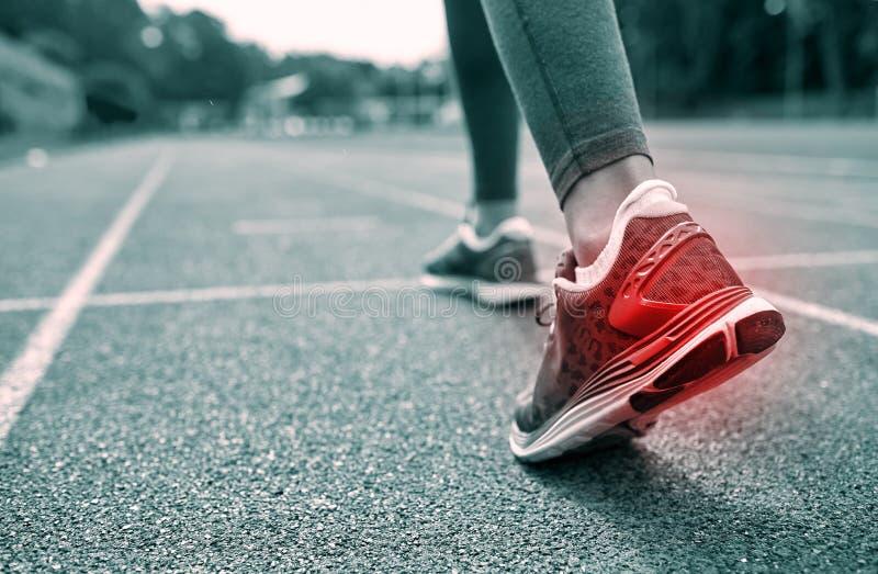 Fermez-vous des pieds avec la tache rouge fonctionnant sur la voie photographie stock libre de droits
