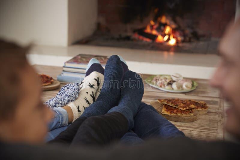 Fermez-vous des pieds comme la famille détendent à côté du feu ouvert image stock