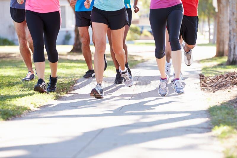 Fermez-vous des pieds de coureurs sur la rue suburbaine photos stock