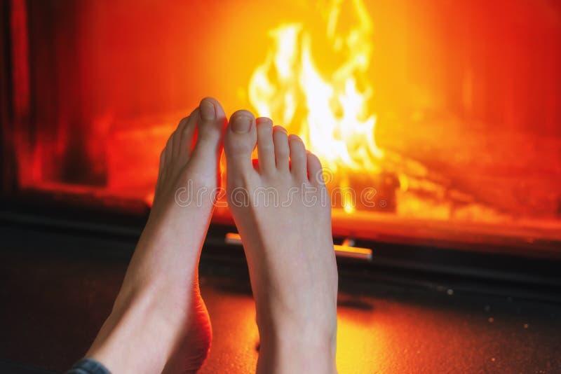 Fermez-vous des pieds du ` s de fille devant la cheminée image stock