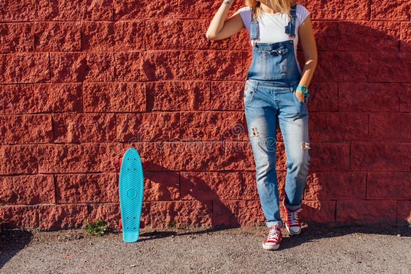 Fermez-vous des pieds et du panneau bleu de patin de penny avec les roues roses image stock