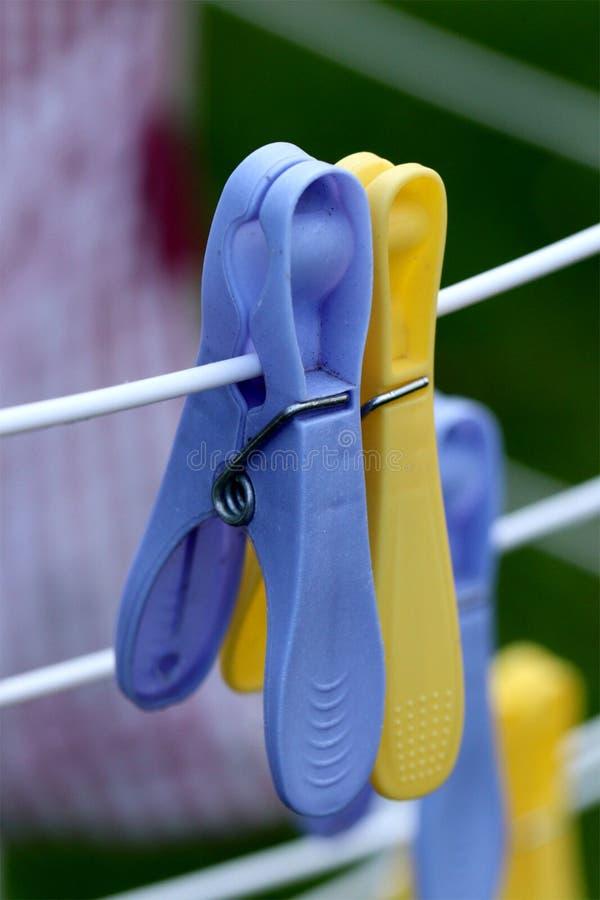 Fermez-vous des pinces à linge bleues et jaunes images stock