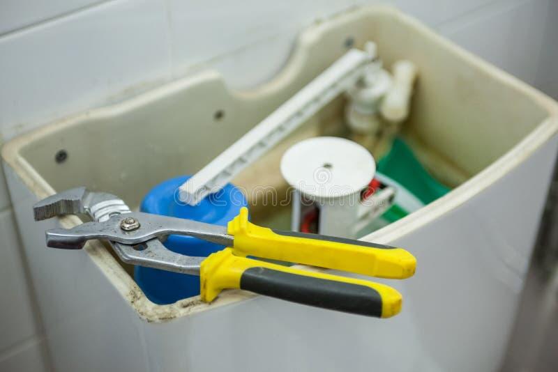 Fermez-vous des pinces se trouvant sur la toilette images stock