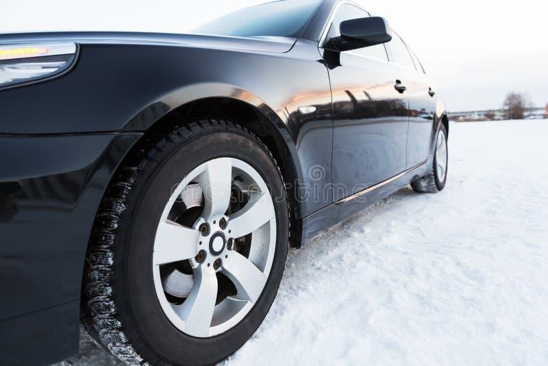 Fermez-vous des pneus de voiture sur la route d'hiver image stock