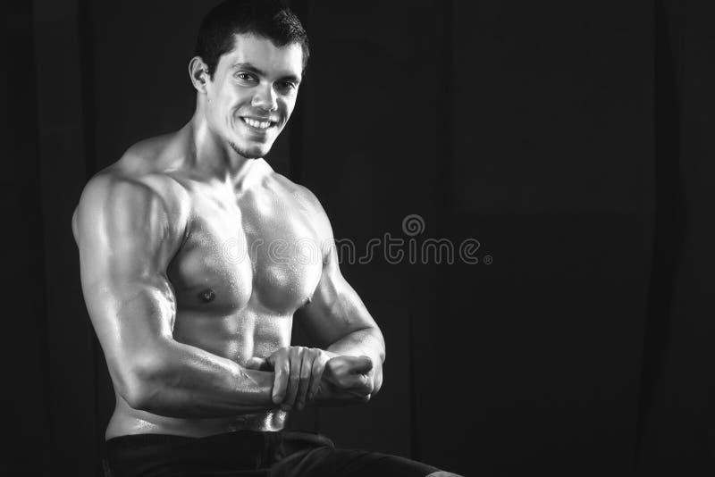 Fermez-vous des poids de levage de jeune homme musculaire au-dessus de l'obscurité photos stock